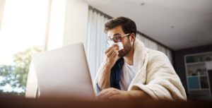 Young man working at home because of flu